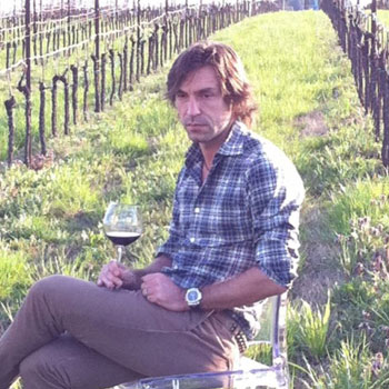 Andrea Pirlo enjoys a glass of wine in one of his vineyards