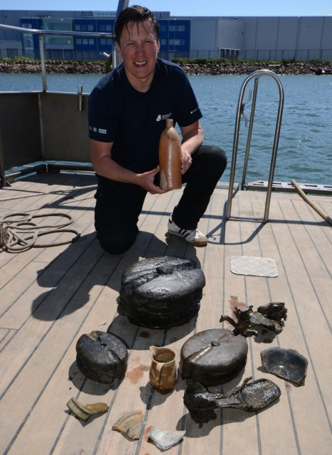 Tomasz Bednarz, an underwater archaeologist the National Maritime Museum, holds the 200-year-old Selters bottle with other shipwreck finds in front of him. Credit: National Maritime Museum, Gdańsk